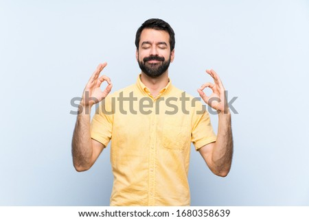 Young man with beard over isolated blue background in zen pose #1680358639