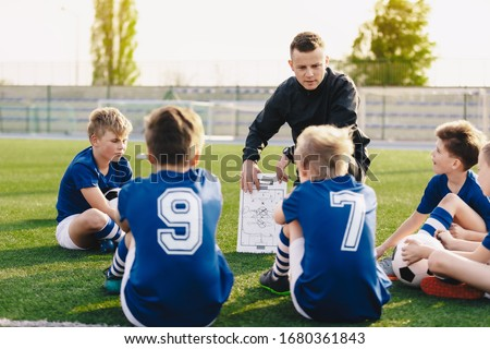 Young coach teaching kids on football field. Football coach coaching children. Soccer football training session for children. Football tactic education. Coach explains a game strategy using board Royalty-Free Stock Photo #1680361843