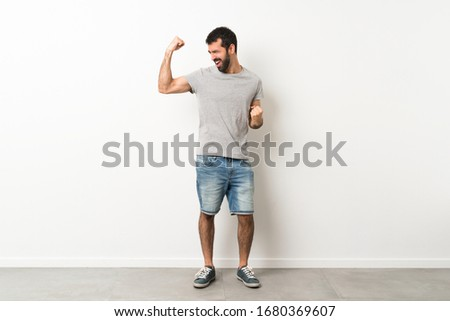A full-length shot of handsome man with beard celebrating a victory #1680369607