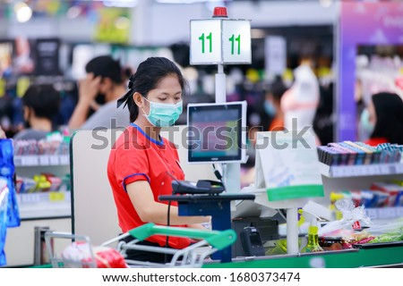 Cashier or supermarket staff in medical protective mask working at supermarket.covid-19 spreading outbreak   #1680373474