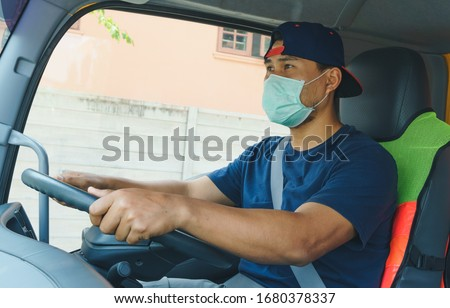Photos of Asian truck drivers wearing masks to protect against dust and the spread of COVID 19 in front of the car. Safety ideas for a worker in the transportation business. And is a new normal life. #1680378337