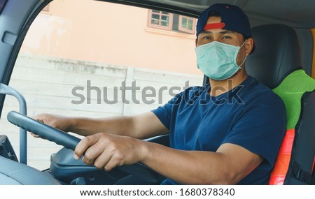 Photos of Asian truck drivers wearing masks to protect against dust and the spread of COVID 19 in front of the car. Safety ideas for a worker in the transportation business. And is a new normal life. #1680378340
