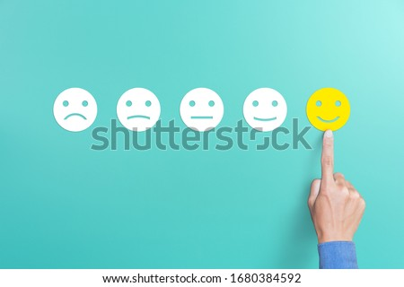 client's hand picked the happy face smile face, Customer service evaluation and satisfaction survey concept. copy space #1680384592