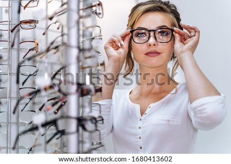 Row of glasses at an opticians. Eyeglasses shop. Stand with glasses in the store of optics. Woman chooses spectacles. Eyesight correction. Royalty-Free Stock Photo #1680413602