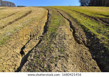 Massive soil erosion landscape field and road destruction by erosive process of water, environmental damage. #1680421456