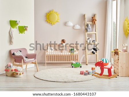 Modern baby room, wooden detail, cradle and crib, pink chair, cabinet, toy yellow sun. Baby in the bed.