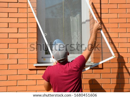 A worker is installing a window mosquito net, fly screen or insects screen to protect the house from insects in summer. #1680451606