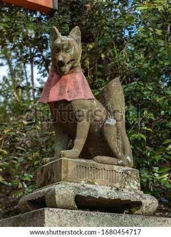 A picture of a fox sculpture at the Fushimi Inari Taisha shrine.