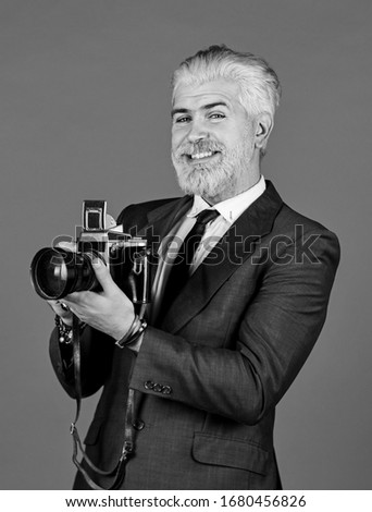 Photographer hold retro camera. Connoisseur of vintage values. Classy and old school. Manual settings. Photographer with blond beard and mustache. Content creator. Man bearded hipster photographer.