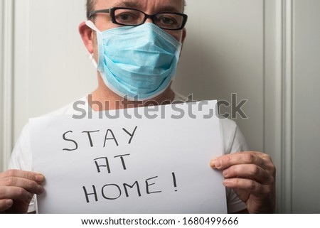 Portrait of doctor wearing medical mask to protect against the corona virus with prevention message : stay at home #1680499666