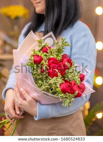 A bouquet of red peonies in florists hands. Fresh beautiful bouquet. #1680524833
