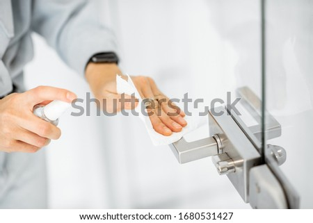 Woman in protective gloves disinfecting door handle while cleaning at home, close-up view on hands. Concept of prevention of virus spread during an epidemic #1680531427