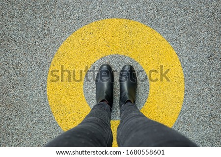 Black shoes standing in yellow circle on the asphalt concrete floor. Comfort zone or frame concept. Feet standing inside comfort zone circle #1680558601