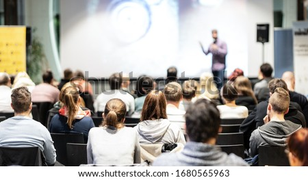 Speaker giving a talk in conference hall at business event. Rear view of unrecognizable people in audience at the conference hall. Business and entrepreneurship concept. Royalty-Free Stock Photo #1680565963