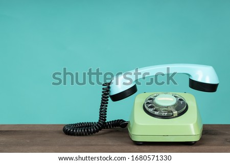 Old telephone on wooden table in front of green background. Vintage phone with taken off receiver. Vintage style photo.  Royalty-Free Stock Photo #1680571330