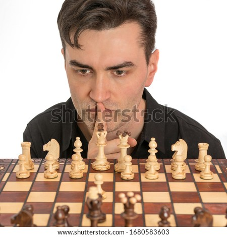 Caucasian man thinking about his second move in a game of chess. Royalty free stock photo.