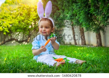 Little baby boy with pleasure celebrating Easter, wearing funny furry bunny ears and enjoying bright sunny day on the backyard, happy spring holiday #1680620878