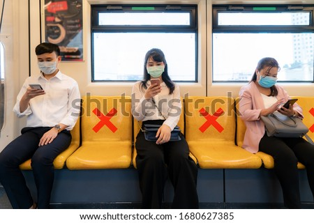 Three Asian people wearing mask sitting in subway distance for one seat from other people keep distance protect from COVID-19 viruses and people social distancing  for infection risk  #1680627385