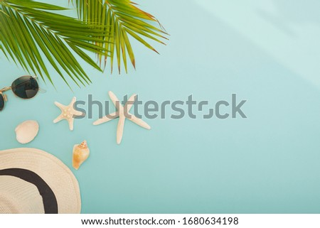 Summer beach vacation.The palm leaf on the blue background. Top view. Straw hat with picture frame .Space for text.White starfish and sunglasses.