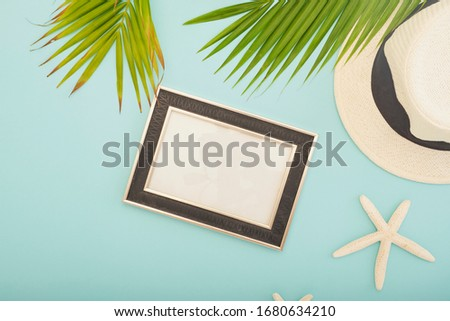 Summer beach vacation.The palm leaf on the blue background. Top view. Straw hat with picture frame .Space for text.White starfish.