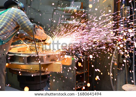 workers in safety clothing sanding a casting in an industrial company  Royalty-Free Stock Photo #1680641494