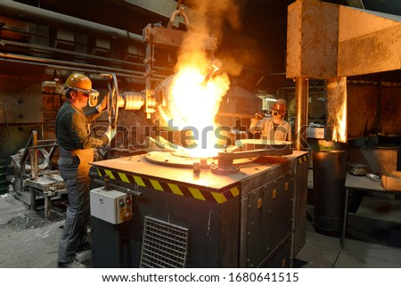 workers in a foundry casting a metal workpiece - safety at work and teamwork  #1680641515