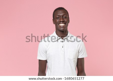 Smiling young african american man guy in white polo shirt posing isolated on pastel pink background studio portrait. People sincere emotions lifestyle concept. Mock up copy space. Looking camera