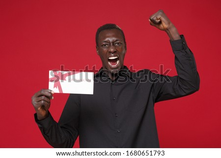 Screaming young african american man guy in classic black shirt posing isolated on red background in studio. People lifestyle concept. Mock up copy space. Hold gift certificate doing winner gesture #1680651793