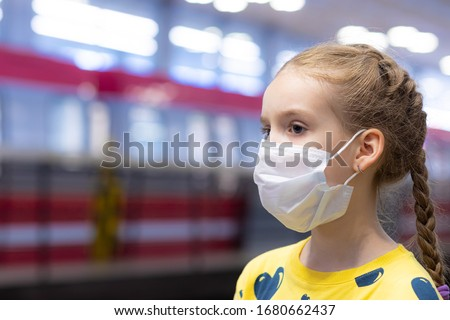 Glad and happy beautiful joy child in the medical helthcare guarding or protecting mask and in yellow t-shirt in the tube, subway or underground hall #1680662437