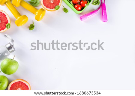 Fitness and healthy food lifestyle concept. Dumbbells, diet fruit and vegetable lunch box, water and jump rope on white background. Flatlay image, top view copy space Royalty-Free Stock Photo #1680673534