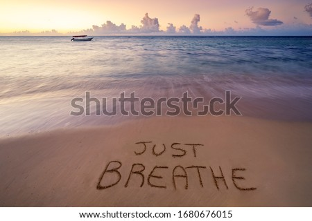Handwritten Just breathe on sandy beach at sunset,relax and summer concept,Dominican republic beach. Royalty-Free Stock Photo #1680676015