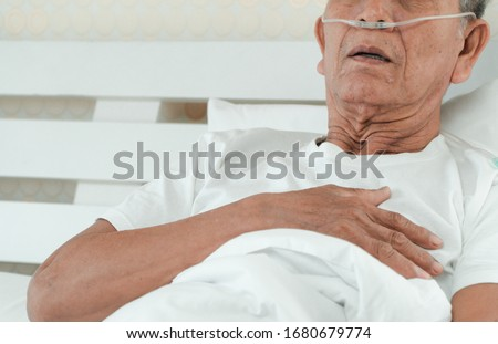 Sad senior man lying on the hospital bed and with a nasal breathing tube for treatment respiratory. Concept of Health care for the elderly, quarantine coronavirus (COVID-19) Royalty-Free Stock Photo #1680679774