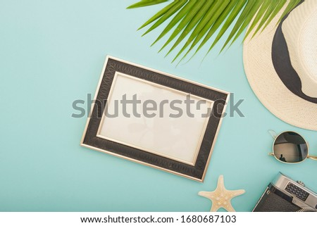Summer beach vacation.The palm leaf on the blue background. Top view. Straw hat with picture frame. Space for text. White starfish and sunglasses. Camera vintage