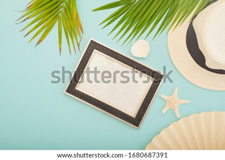 Summer beach vacation.The palm leaf on the blue background. Top view. Straw hat with picture frame .Space for text.White starfish and blow