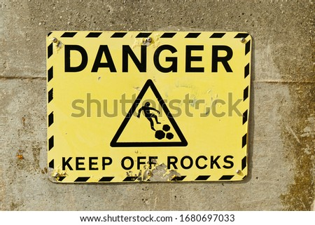 UK England A yellow Danger Keep Off The Rocks warning sign on the Essex coast England United Kingdom.