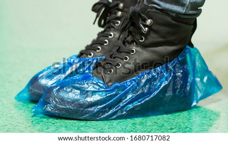 Blue medical shoe covers are worn over shoes on the floor,  hygiene and cleanliness in medical institutions. Selective focus #1680717082