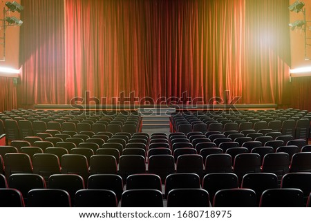 Large illuminated theatre hall with empty seats viewed from the rear looking towards the stage with its closed red curtain in a performing arts concept #1680718975