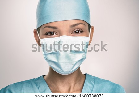 COVID-19 Coronavirus pandemic happy Asian doctor positive with hope wearing surgical mask and blue protective scrubs at hospital. Inspiring confidence in the future to solve the crisis. #1680738073