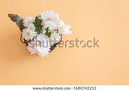 The background is solid color with bright white flowers in a small basket. The view from the top, place for text.