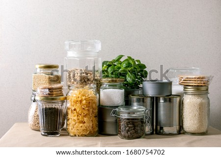 Food supplies crisis food stock for quarantine isolation period. Different glass jars with grains, pasta, cans of canned food, toilet paper, chalkboard handwritten chalk lettering Stay home and relax. #1680754702