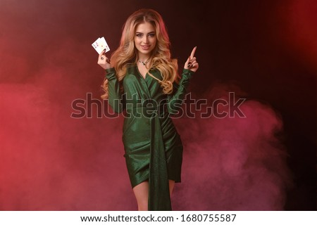 Blonde girl in green dress, jewelry. Smiling, showing two aces, pointing at something, posing on colorful smoky background. Poker, casino. Close-up Royalty-Free Stock Photo #1680755587
