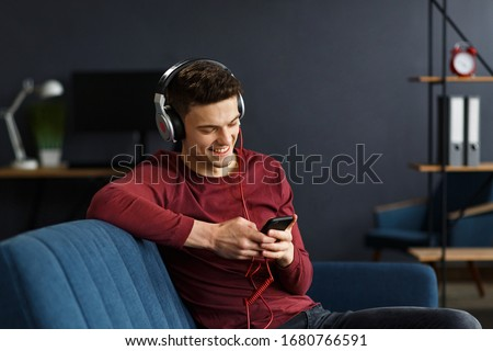 Enjoy listening to music.Young man in headphones listening music on smart phone using music app. Portrait of guy in earphones and mobile phone at home. Relaxation, leisure and stress management. #1680766591