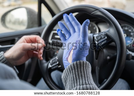 Man puts on rubber gloves for protect himself from bacteria and virus while driving a car. Coronavirus. Pandemic #1680788128