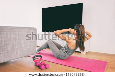 Home fitness woman doing strength training abs situps bodyweight floor exercises watching online livestream workout web videos casted on smart tv in living room of house or apartment. #1680788584