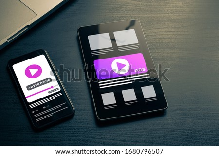 Video Advertising with Digital Marketing business concept. Soft focus on the smartphone and Tablet PC lying on a dark wooden table with ads media on the screen. Online broadcasting, streaming video Royalty-Free Stock Photo #1680796507