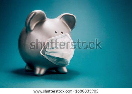 Close up of piggy bank, wearing protective face mask, isolated on blue background. Money saving concept in time of coronavirus pandemic. Royalty-Free Stock Photo #1680833905