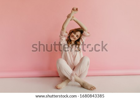 Lovely young woman with wavy blond hair in modern pink pajamas smiling with closed eyes on isolated background. Lady in tight outfit sitting on floor..