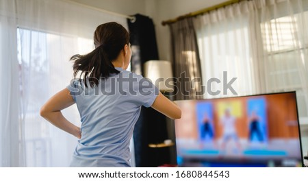 Fitness online Stay home.home fitness workout class live streaming online.Asian woman doing strength training cardio aerobic run exercises.Watching videos on a smart tv in the living room at home. #1680844543