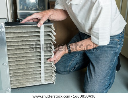 Senior caucasian man changing a folded dirty air filter in the HVAC furnace system in basement of home #1680850438