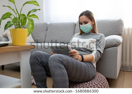 Woman using tablet on a home couch. Woman surfing on line or working from home concept. Woman at home using medical mask #1680886300